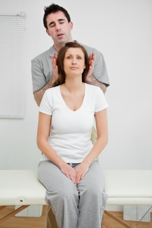 Woman sitting while being manipulated in a medical room Stock Photo - 16204989