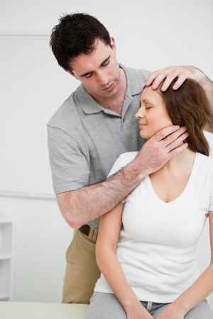 osteopath: Osteopath insuring central alignment of spine in a medical room