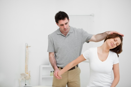 neuromuscular reeducation: Osteopath stretching the arm of a woman in a medical room