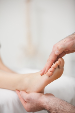 muscle retraining: Doctor offering a foot massage in a medical room