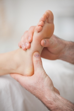 muscle retraining: Foot receiving a massage by a physiotherapist in a medical room