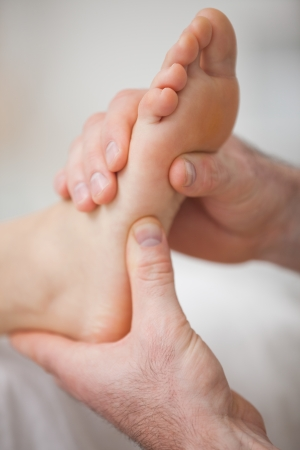 neuromuscular reeducation: Close-up of two hands massaging a foot in a room