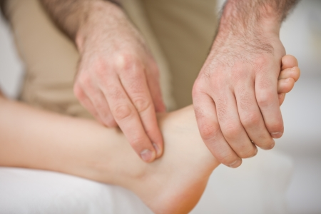 neuromuscular: Two fingers touching and massaging a foot indoors