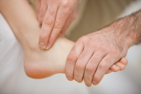 mobilization: Physiotherapist massaging a barefoot indoors