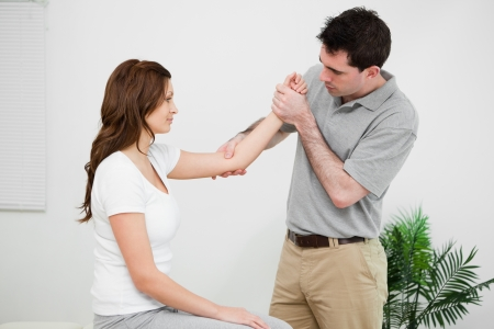 joint mobilization: Serious practitioner touching the elbow of a woman in a medical room