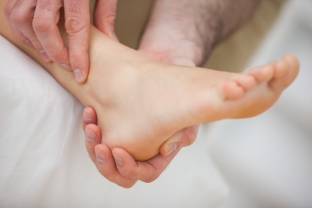 muscle retraining: Barefoot being massaged by a doctor indoors Stock Photo