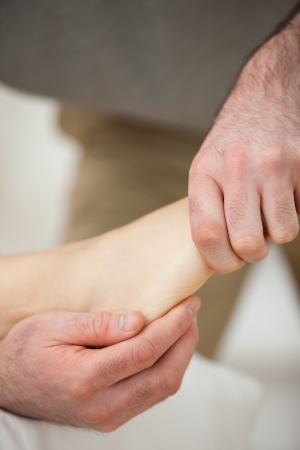 muscle retraining: Barefoot being stretched by a doctor indoors Stock Photo