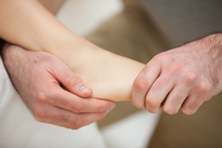 neuromuscular reeducation: Foot being stretched by a physiotherapist in a room Stock Photo
