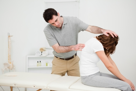 Physiotherapist looking at the spinal column of a woman in a medical room