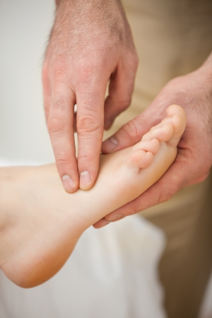 joint mobilization: Two fingers palpating the muscles of a foot indoors