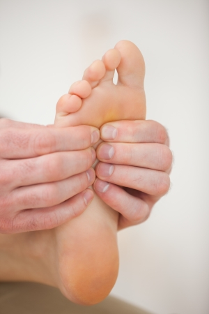 neuromuscular reeducation: Barefoot being massaged by a physiotherapist in a room