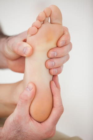 neuromuscular: Physiotherapist working on a barefoot in a room Stock Photo