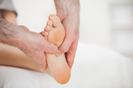 neuromuscular reeducation: Physiotherapist using his fingers to massage a foot in a room