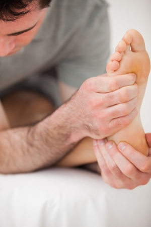 Serious physiotherapist making a joint mobilisation indoors Stock Photo - 16207310