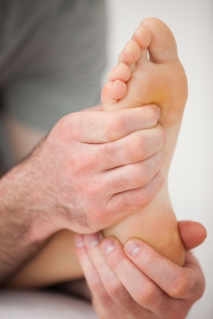 neuromuscular reeducation: Hands of a practitioner holding a barefoot in a room Stock Photo
