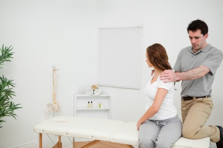 neuromuscular reeducation: Osteopath looking at the back of a woman in a medical room