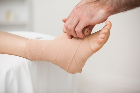 dislocation: Practitioner bandaging an ankle in a medical room Stock Photo