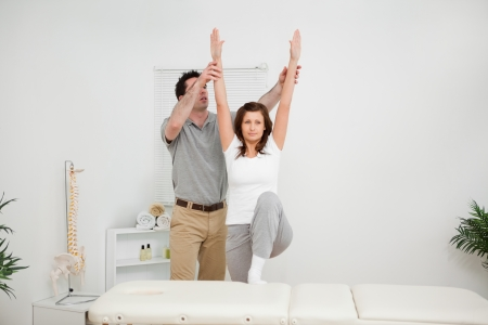 Brunette doing stretching exercises with a physiotherapist in a room Stock Photo - 16203611