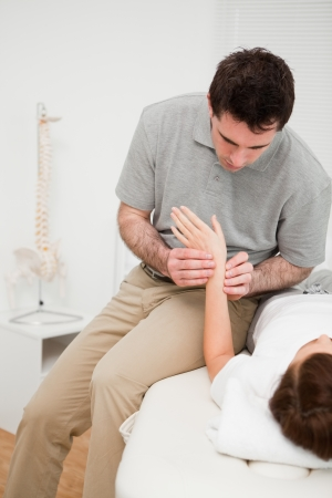 naprapathy: Physiotherapist placing his fingers on the hand of a patient in a room
