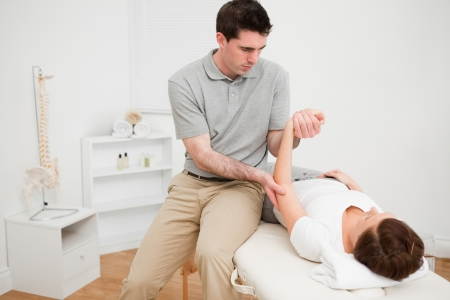 joint mobilization: Physiotherapist holding the arm of a brunette woman in a room