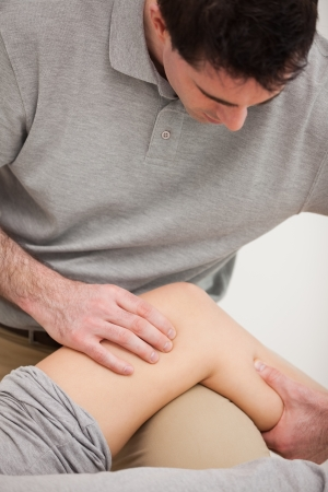 Physiotherapist looking at the knee of his patient indoors photo