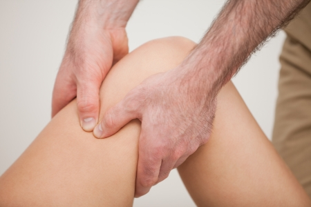 lower limb: Knee of a patient being held by a physiotherapist in a room Stock Photo