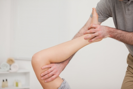 neuromuscular reeducation: Leg being stretched by a doctor in a physio room