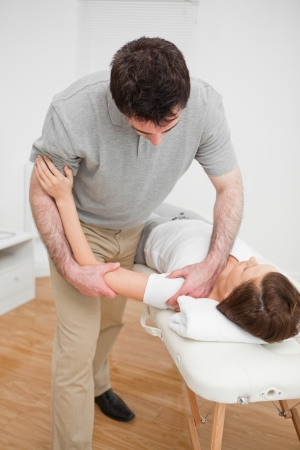 neuromuscular reeducation: Osteopath working on a shoulder of a patient in a room Stock Photo