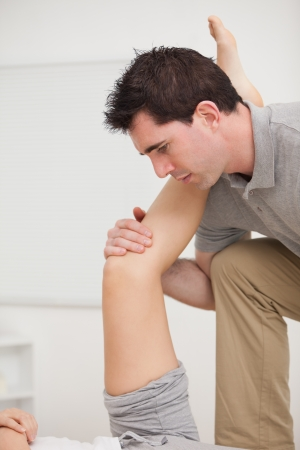 joint mobilization: Serious osteopath holding a leg in a room Stock Photo