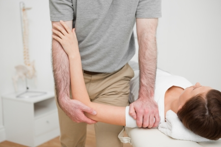 muscle retraining: Physiotherapist pressing the shoulder of a woman in a medical room Stock Photo