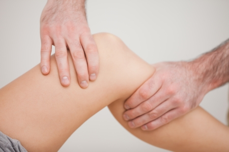 kneecap: Knee of a patient being touched by a practitioner in a room
