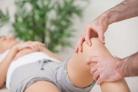 Practitioner using his fingers to massage a knee in a room photo