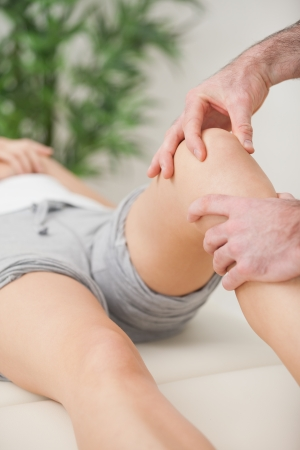 lower limb: Fingers massaging the knee of a patient in a room