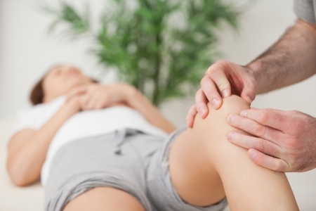osteopath: Knee of a woman being touched by a doctor in a room