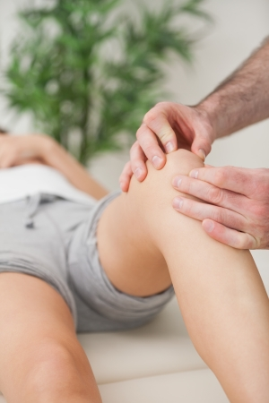 Fingers of a doctor massaging a leg in a room Stock Photo - 16207003