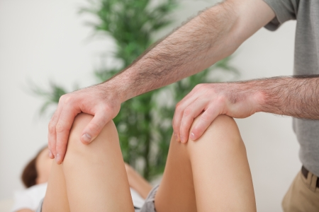 Knees of a patient being held by a doctor in a room photo