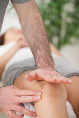 Physiotherapist using his hand palm to massage a knee indoors photo