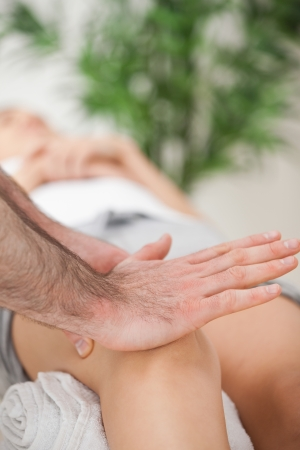 Osteopath using his hand palm to massage a knee in a medical room photo