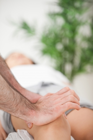 lower limb: Serious doctor pressing on the knee of a woman indoors