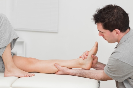 Seus doctor massaging a calf on a medical table indoors Stock Photo - 16204430