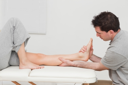 neuromuscular reeducation: Calf of a patient being massaged by a physiotherapist in a room Stock Photo