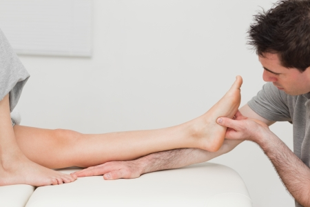 Physiotherapist looking at the foot of a patient in a room photo