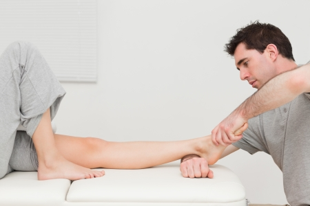 Serious doctor stretching the foot of his patient in a room photo