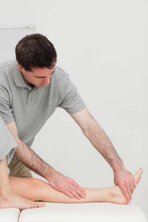 joint mobilization: Serious physiotherapist working on the calf of a patient in a room