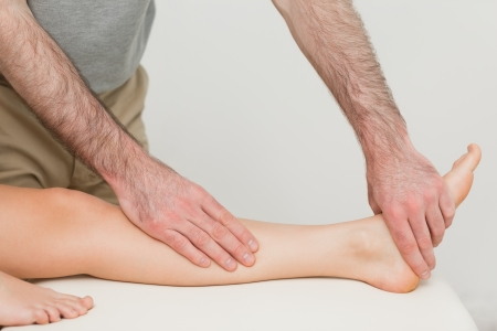 muscle retraining: Physiotherapist touching the calf and the foot of a patient in a room