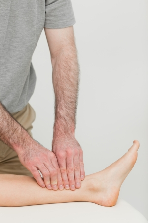 muscle retraining: Fingertips massaging a shin bone in a room