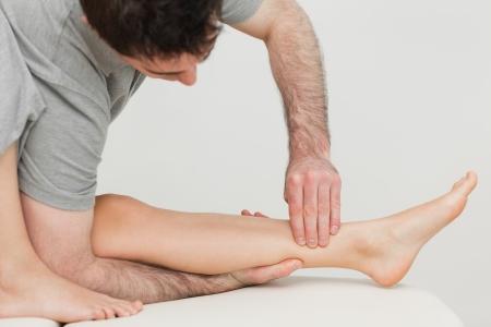 osteopata: Oste�pata grave masajear el hueso de la espinilla de un paciente en una sala de