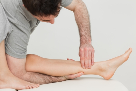 shin bone: Serious osteopath massaging the shin bone of a patient in a room