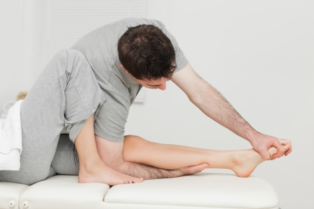 joint mobilization: Brunette osteopath stretching a foot in a medical room Stock Photo