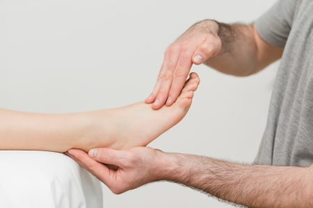 neuromuscular reeducation: Doctor holding the foot of a patient in a room Stock Photo